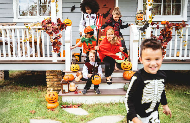 Group of children running away from a house while trick-or-treating