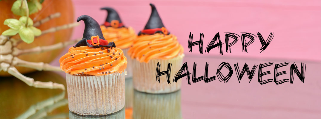 Cupcakes with orange frosting next to black happy halloween text against a pink background