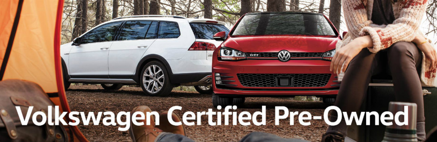 """Image of two Volkswagen vehicles parked at a campsite with two people siting in a tent and """"Volkswagen Certified Pre-Owned"""" white text at the bottom of the image"""
