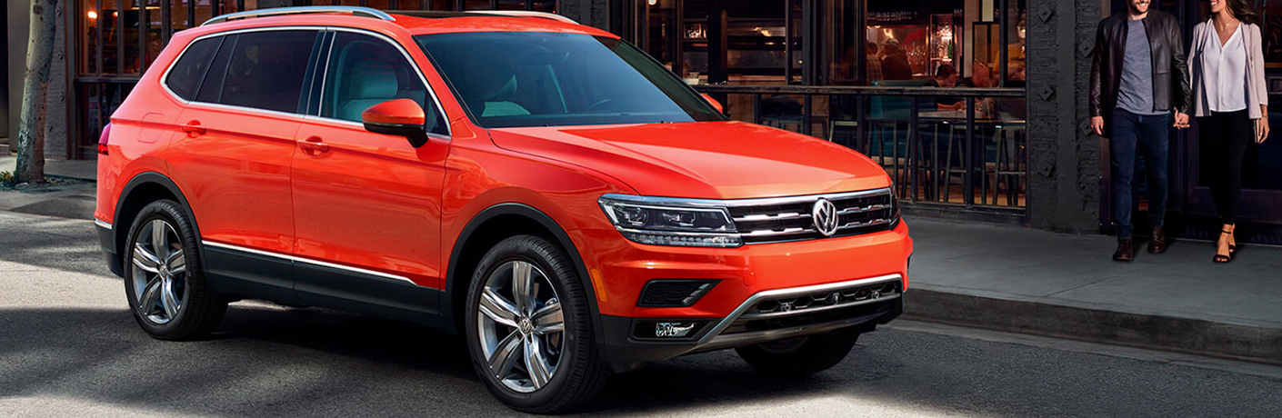 Exterior view of an orange 2019 Volkswagen Tiguan parked on a city street