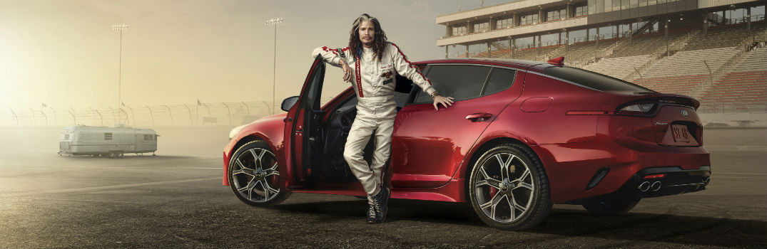 Aerosmith Steven Tyler next to 2018 Kia Stinger on Race Track