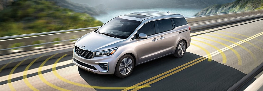 2020 Kia Sedona driving in front of water and mountains showing the radar on safety features