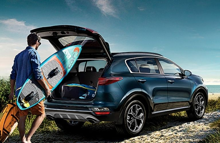 View of the cargo space of the 2022 Kia Sportage with a man standing before it