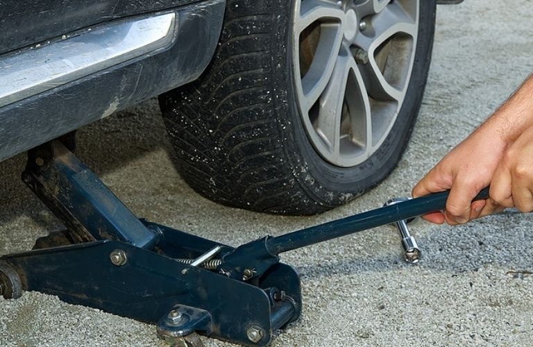 Image of a person using a jack to raise the car to change the flat tire