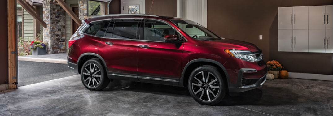 Passenger side exterior view of a red 2019 Honda Pilot
