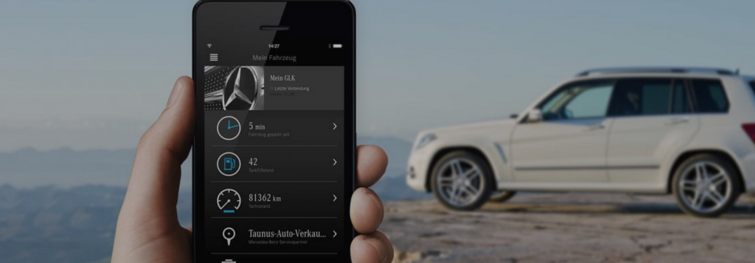 mercedes-benz app used in front of a new mercedes-benz suv model