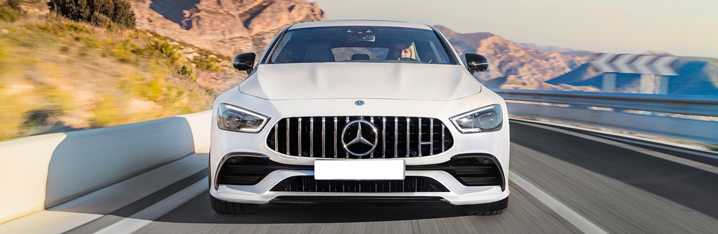 Exterior view of a white 2019 Mercedes-AMG GT 4-Door Coupe driving down a highway