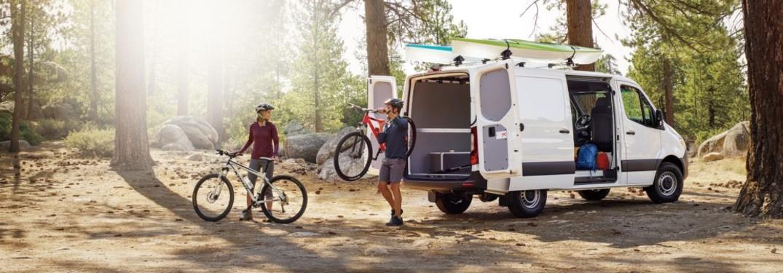 Mercedes-Benz van with bikes and people