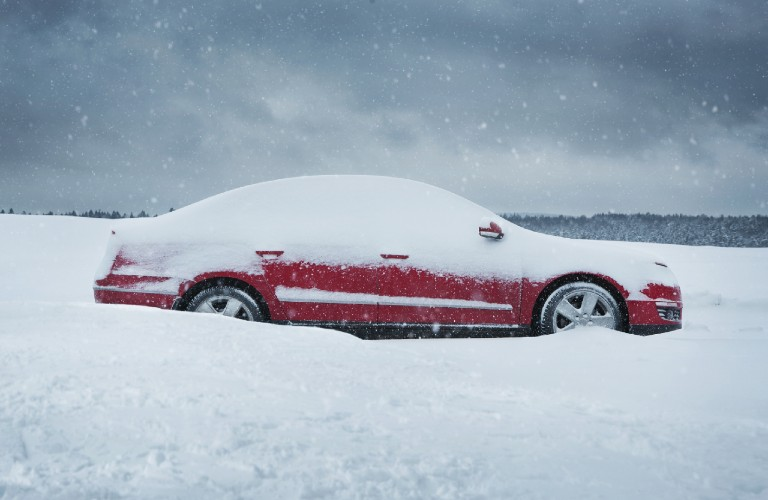 red car in a lot of snow