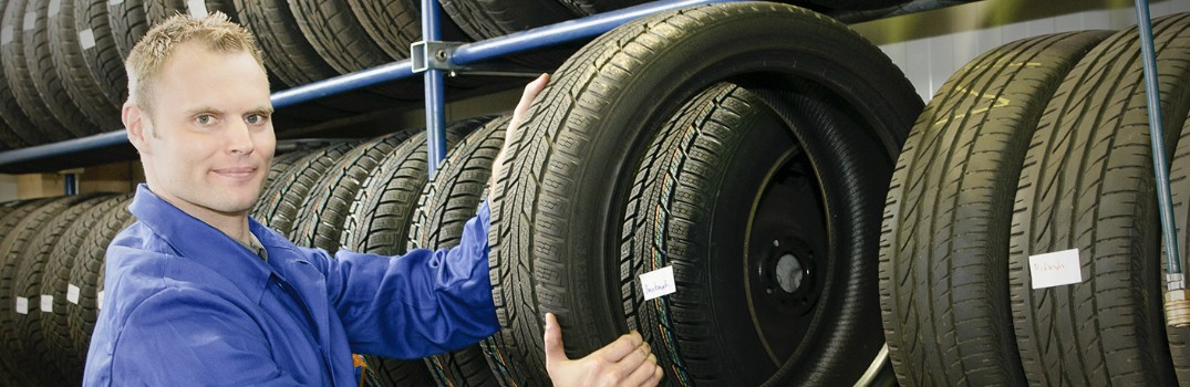 man smiling and holding a tire