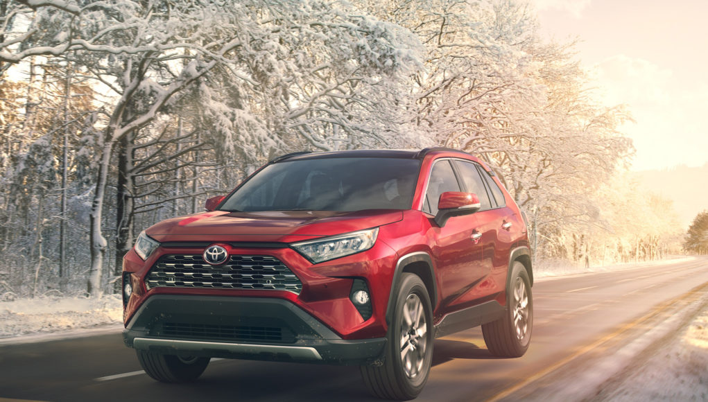 Image of a red 2019 Toyota RAV4 driving on a road in winter.