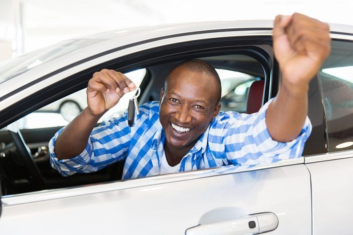 Image of an excited man in a car, holding his keys.