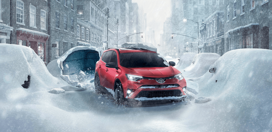 Image of a red Toyota RAV4 on a snowy city street.