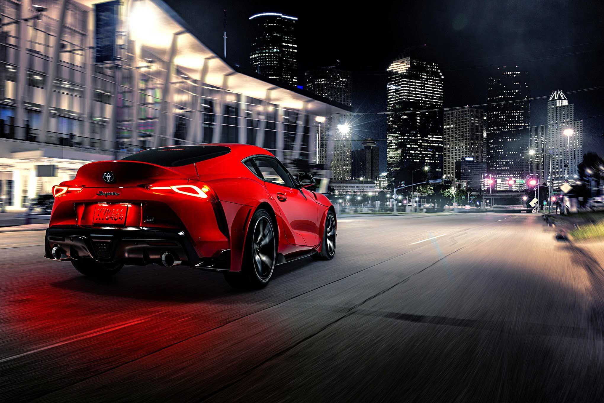 Image of the rear of a red 2020 Toyota Supra driving at night in the city.