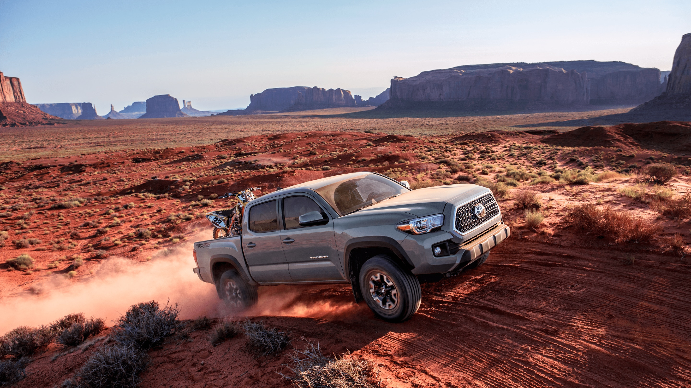 Image of a gray Toyota Tacoma truck driving off-road in the desert.