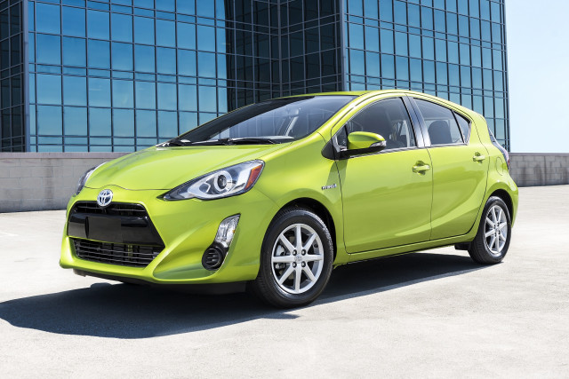 Image of a green 2018 Toyota Prius parked in front of a glass building.