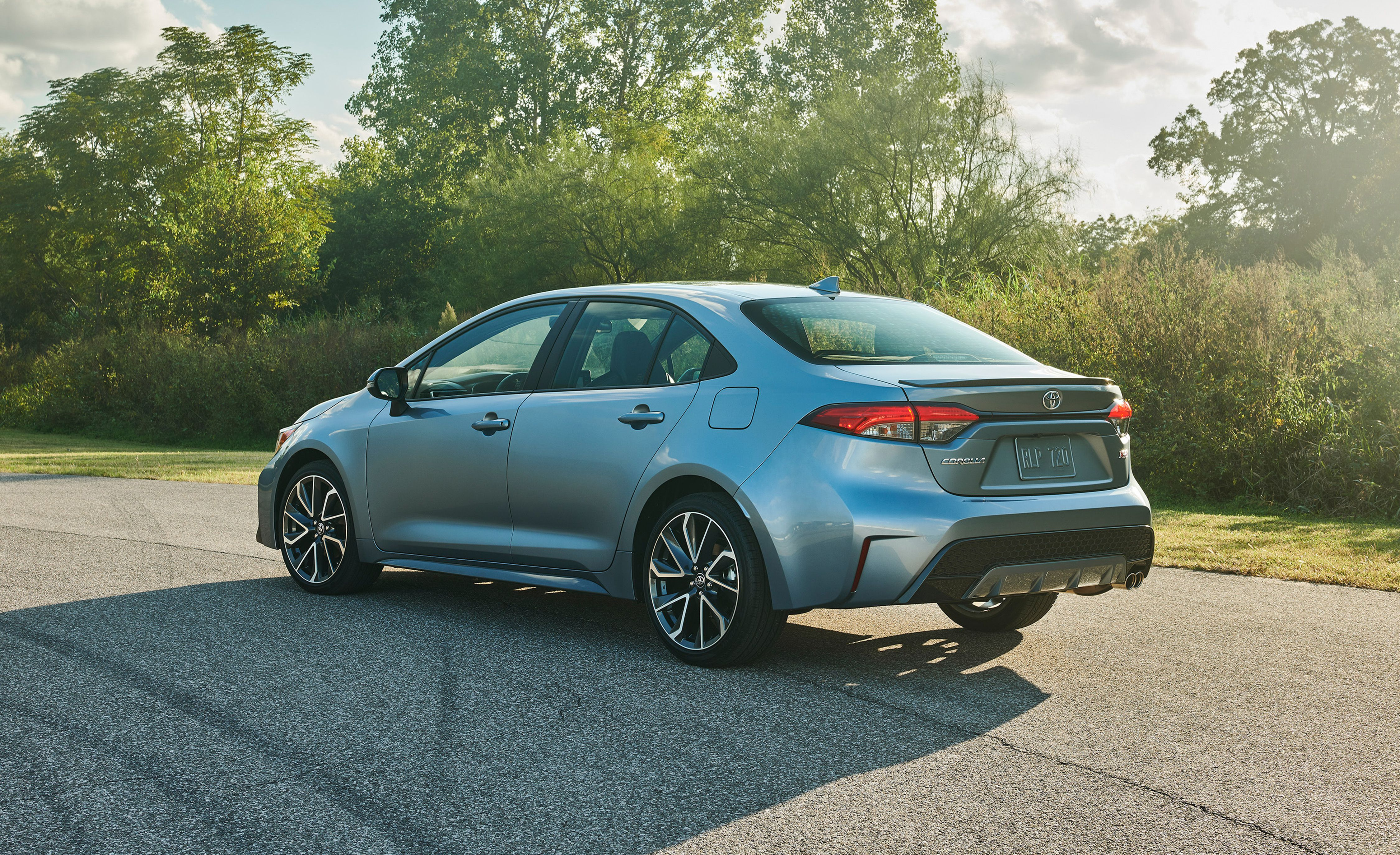 Image of a pale blue 2020 Toyota Corolla parked on a forested road.