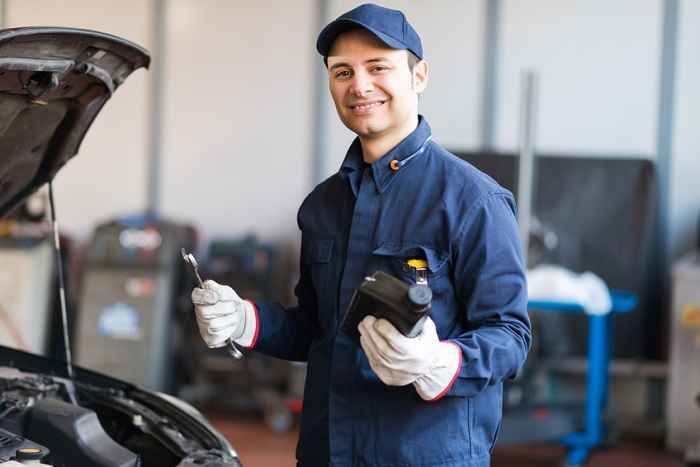Image of a mechanic holding a bottle of engine oil next to a popped hood.