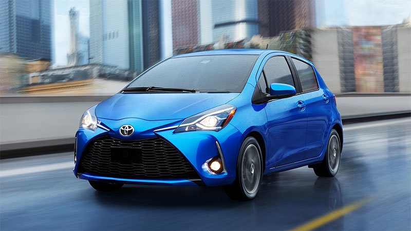 Image of a blue 2020 toyota yaris hatchback driving on a city street.