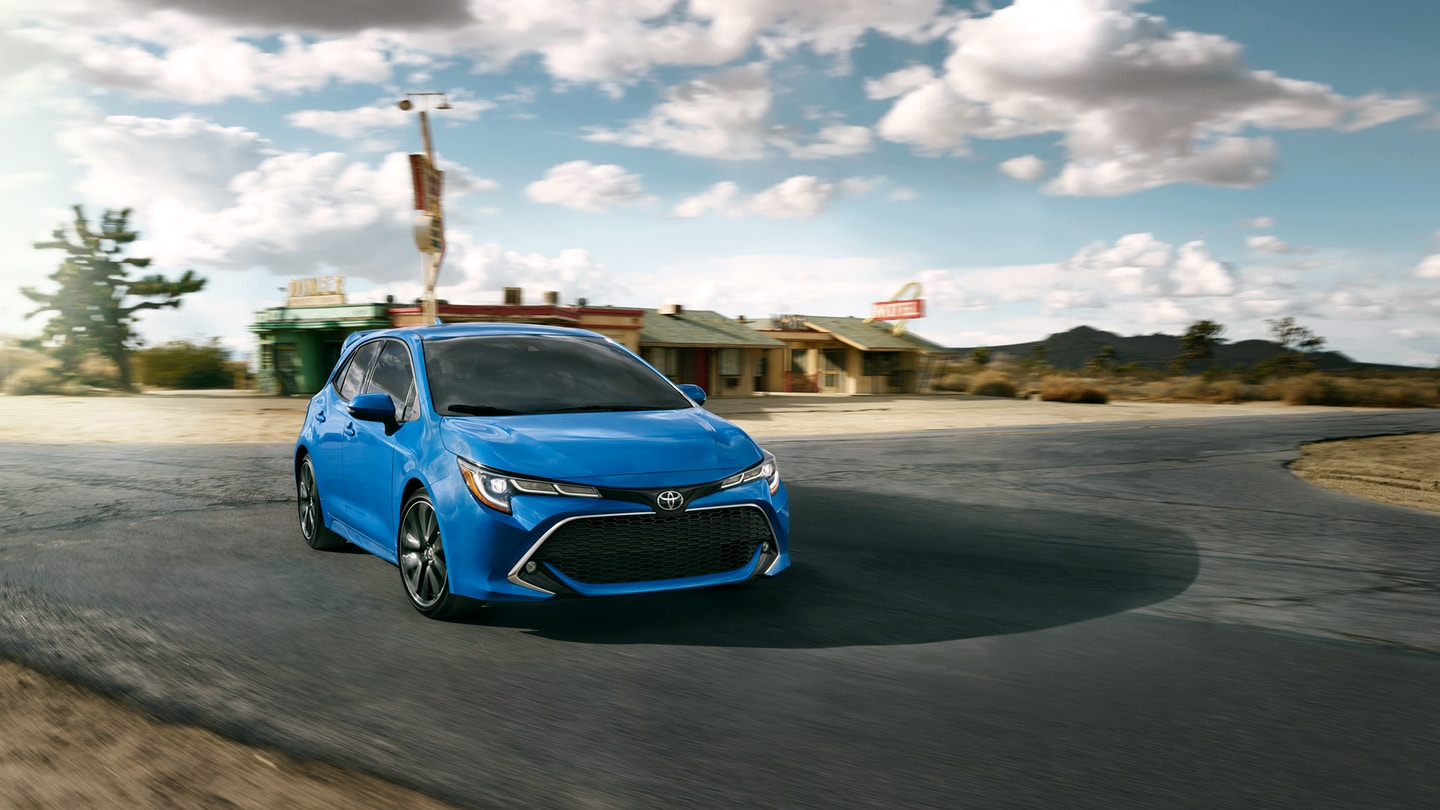 Image of a blue 2019 Toyota Corolla driving on a country highway.
