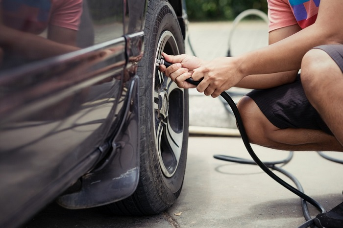 Image of a man checking the tire pressure on his car.