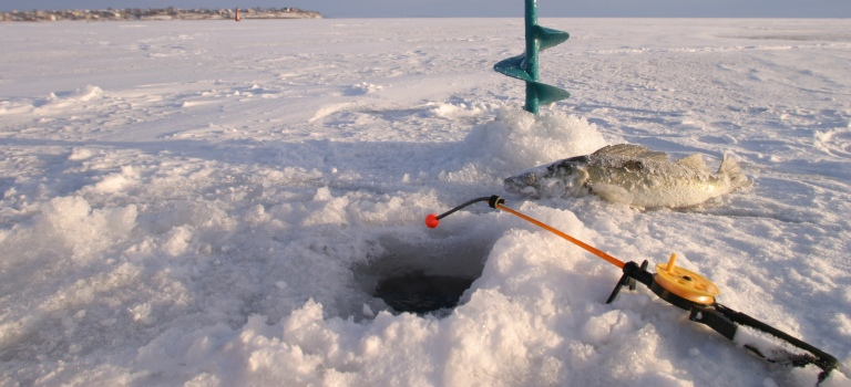 ice fishing with a fish next to the hole