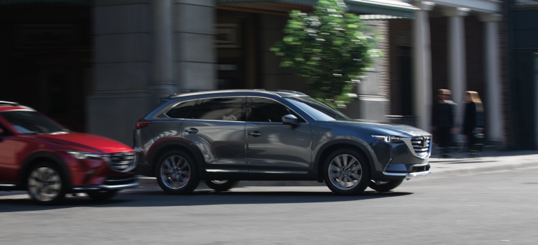 2019 Mazda CX-9 gray side view in an intersection with a red Mazda CX-3