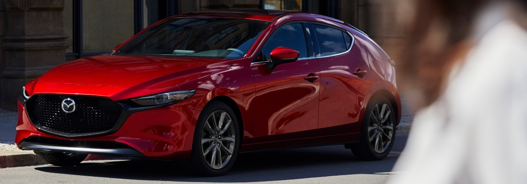 2019 Mazda3 Hatchback red side view with woman in foreground