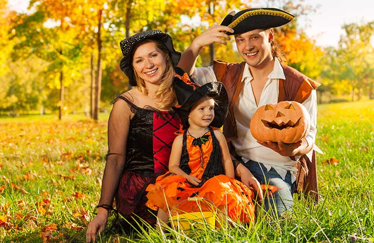Family dressed for Halloween in the grass