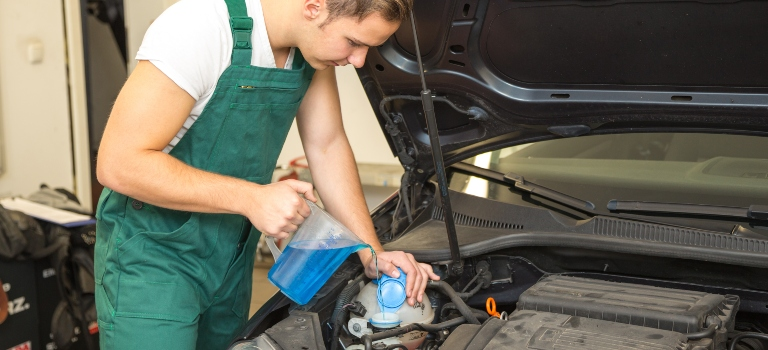man filling car with washer fluid