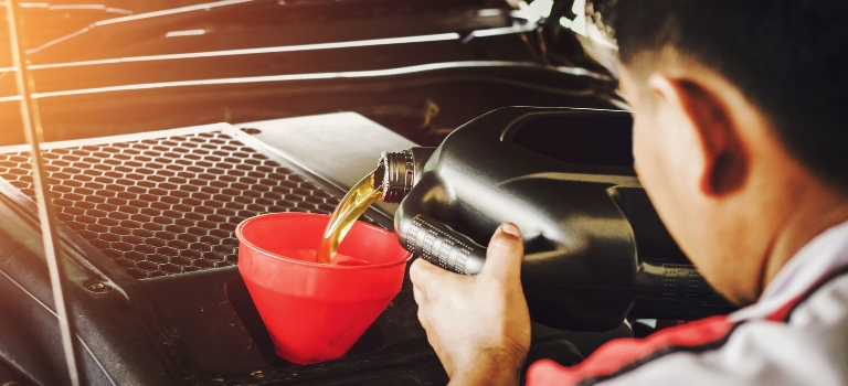 Tech pouring oil into an engine