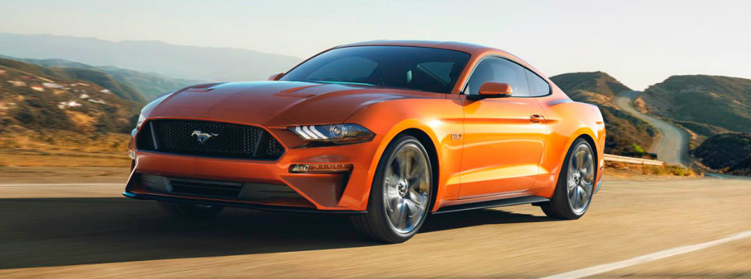 Orange 2018 Ford Mustang cruising along a deserted road