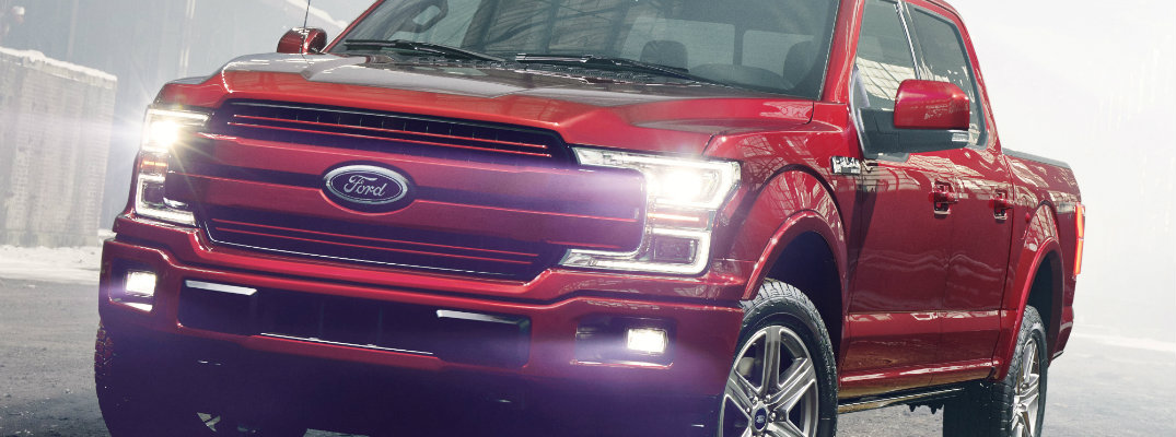 Red 2018 Ford F-150 pickup truck with headlights on