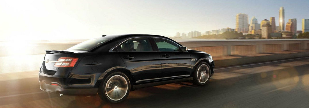 2018-Ford-Taurus-driving-on-highway-in-front-of-city-skyline