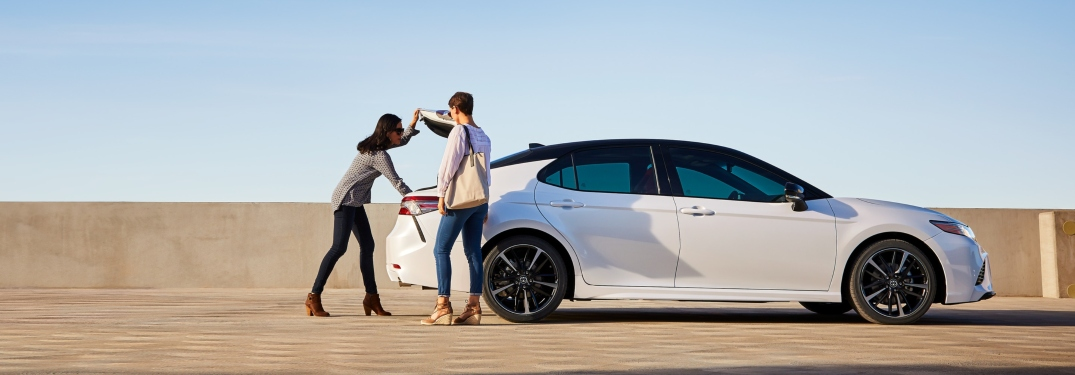 Young couple opening trunk of 2019 Toyota Camry