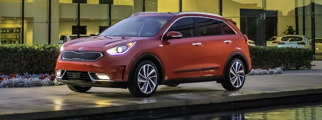 Red 2017 Kia Niro parked in front of glass building at night
