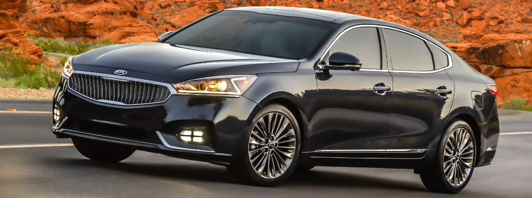 Black 2017 Kia Cadenza on Highway with Red Cliffs in background