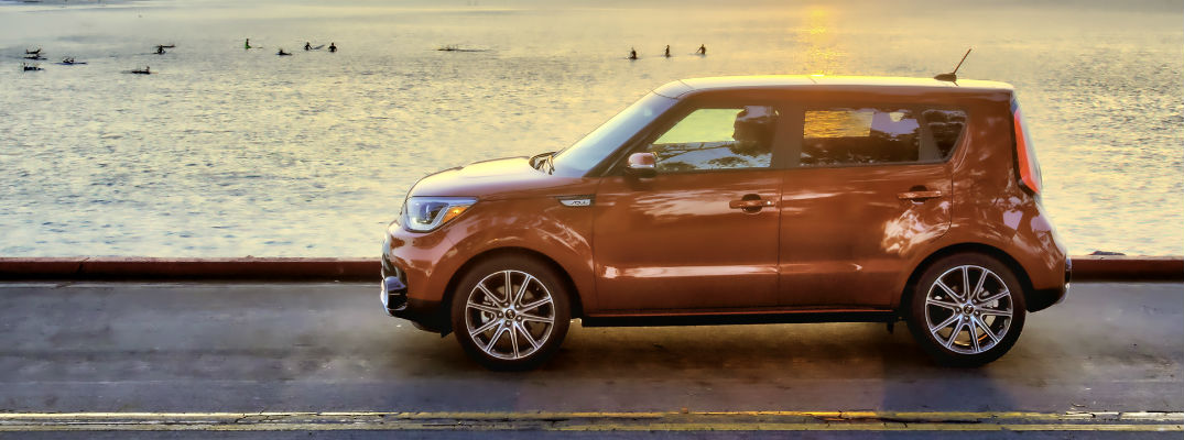 Orange 2017 Kia Soul on beachfront road with water in background