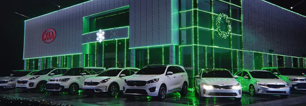 Kia models in front of a decorated Kia dealership