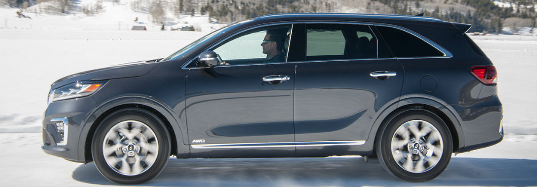 2019 Kia Sorento exterior drivers side profile going fast in snow with man driving