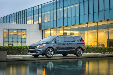 2019 Kia Sedona exterior front fascia and drivers side in front of glass building