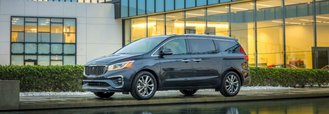 2019 Kia Sedona exterior front fascia and drivers side parked in front of glass window building