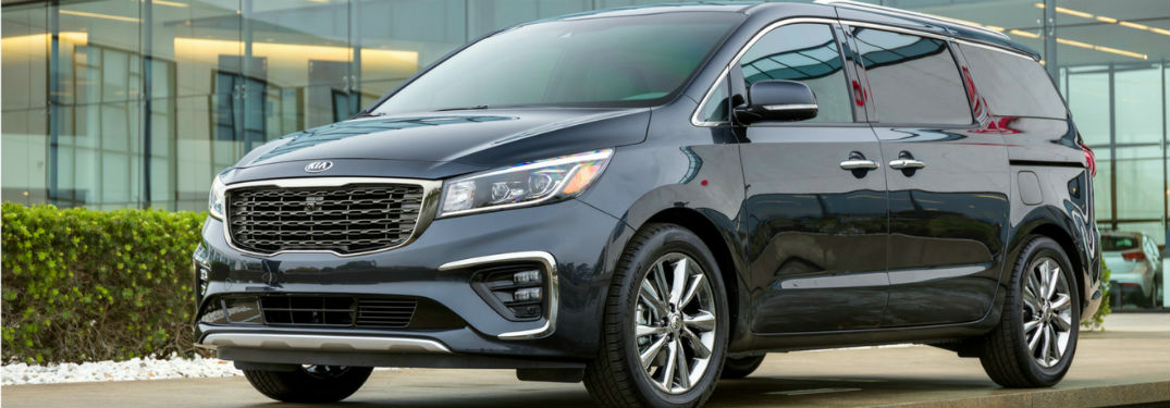 2019 Kia Sedona exterior front fascia and drivers side parked in front of glass windows