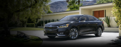 Aurora Black 2018 Kia Cadenza exterior front fascia and drivers side in front of building