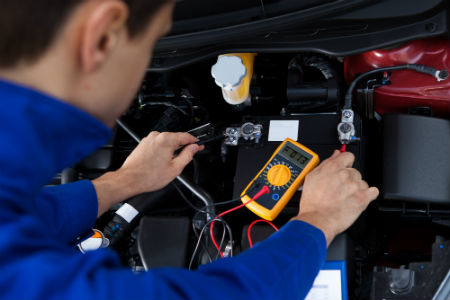 Auto mechanic testing car battery