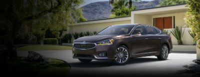 Granite Brown 2018 Kia Cadenza exterior front fascia and drivers side in front of building