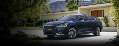 Gravity Blue 2018 Kia Cadenza exterior front fascia and drivers side in front of building