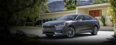 Platinum Graphite 2018 Kia Cadenza exterior front fascia and drivers side in front of building