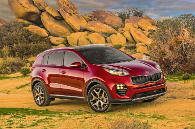 2018 Kia Sportage exterior front fascia and passenger side parked on sandy grass