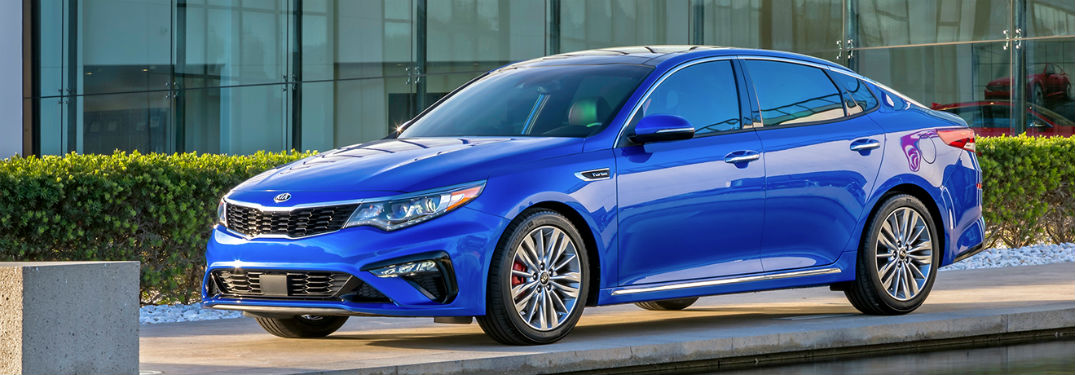 2019 Kia Optima exterior front fascia and drivers side parked in front of glass windows